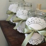 mason jars with satin green ribbon and white doilies