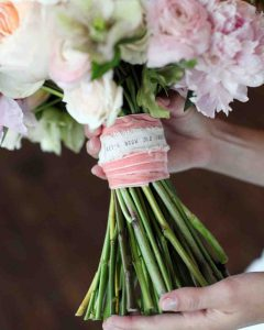 using custom ribbon rolls to tie flower bouquets for weddings and other events