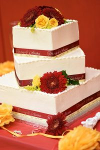 scarlet red and baby mazie satin face ribbon rolls on a wedding cake