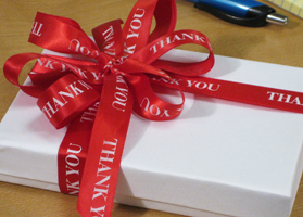 A gift wrapped in a red ribbon that reads Thank You, sitting on an office desk, used to stay socially connected to a team member.