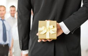 A businessman hiding a corporate gift behind their back as part of the company's effort to give the right corporate gifts.