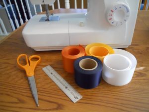 Materials needed to make holiday ribbon stockings include badge ribbons, scissors and a sewing machine.