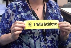 """Woman holding a yellow """"I Will Achieve"""" commitment ribbon."""